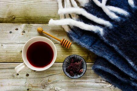 Cup of hibiscus tea on autumn wooden background flat lay Standard-Bild