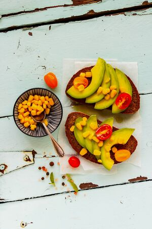 Flat-lay of vegan toasts with avocado and corn on turquoise table from above