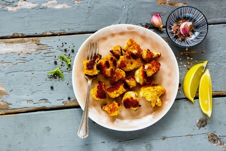 Tasty roast cauliflower in plate on wooden table flat lay. Delicious healthy snack top view