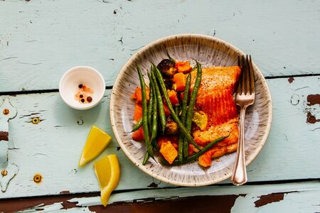 Roast salmon fish with vegetables on turquoise table, flat lay composition