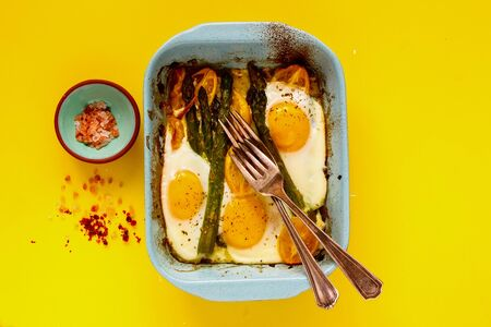 Flat-lay of baked vegetables and eggs on yellow background