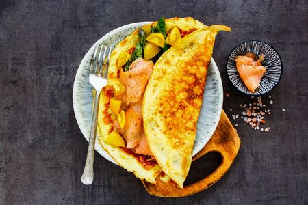 Flat-lay of homemade omelette with smoked salmon in plate Stock Photo
