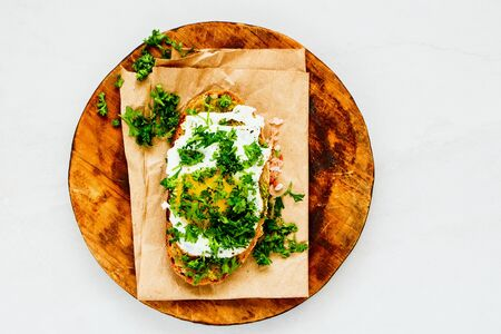 Fried egg on toast with fresh herbs on wooden cutting board Stock Photo