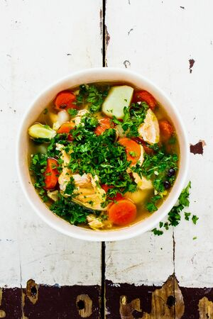 Fish soup with salmon and fresh herbs in bowl close-up