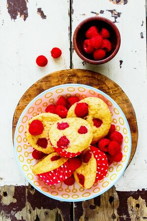 Healthy muffins with fresh raspberries in bowl on wooden table Stock Photo