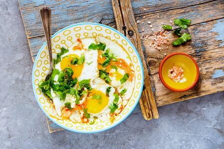 Breakfast with fried eggs and salmon in bowl flat lay