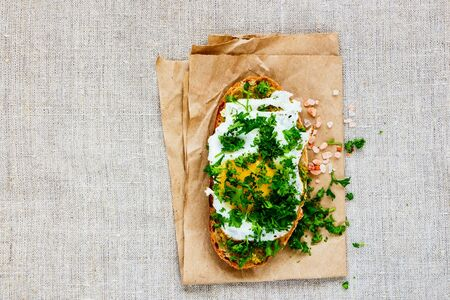 Fried egg on toast with pesto sauce and fresh herbs