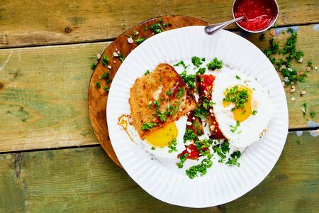 Breakfast with fried eggs and fresh herbs on grilled bread over old wooden table
