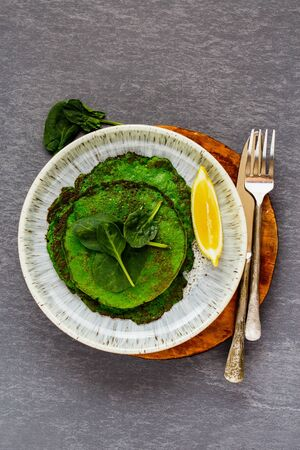 Healthy green spinach pancakes in plate on grey background flat lay