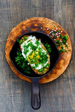 Fried egg on toast with pesto sauce and fresh herbs in frying pan top view