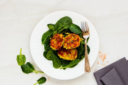 Fresh spinach with healthy vegetable pancakes on plate close-up
