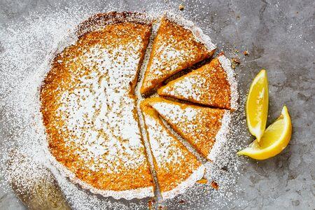 Tasty Sliced Lemon tart sprinkled with icing sugar close up