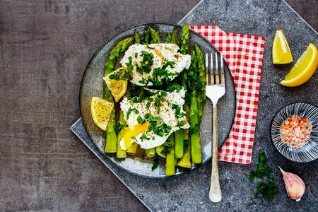 Green aspargus and poached eggs on vintage board close up