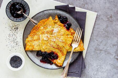 Homemade poppyseed pancakes with wild blueberry jam on light background Stock Photo
