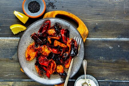 Oven roasted sweet peppers in plate on dark wooden table flat lay Stock Photo