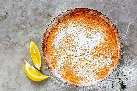 Homemade whole Lemon tart sprinkled with icing sugar on light background Stock Photo