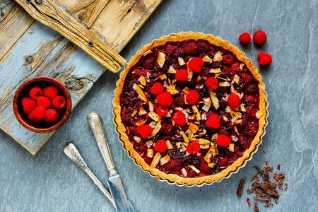 Whole raspberry chocolate tart on light background top view
