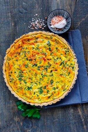 Tasty classic cheese quiche with fresh herbs flat lay