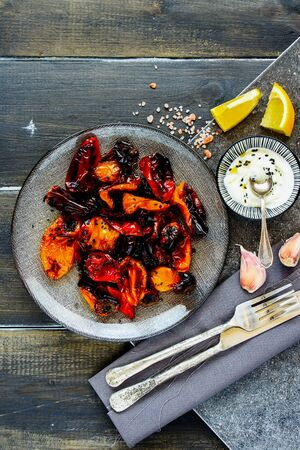 Roasted sweet peppers with yogurt dressing in plate top view Stock Photo
