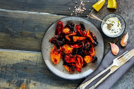 Oven-baked sweet peppers with yogurt dressing in plate top view