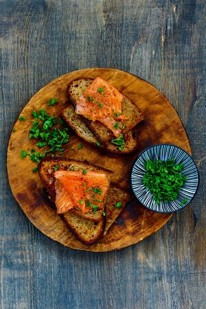 Tasty smoked salmon and herbs on grilled bread on wooden cutting board
