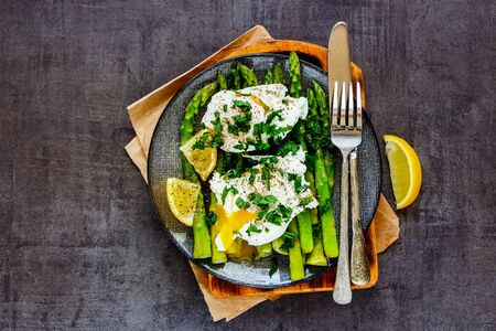 Fresh aspargus and poached eggs in plate flat lay
