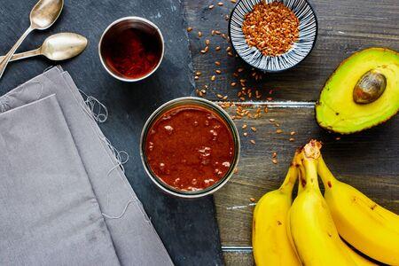 Avocado, chocolate, banana smoothie in jar on dark background flat-lay Stock Photo