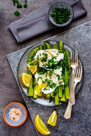 Green aspargus and poached eggs in plate on vintage board