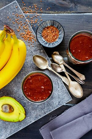 Avocado, chocolate, banana smoothie in jars on dark background