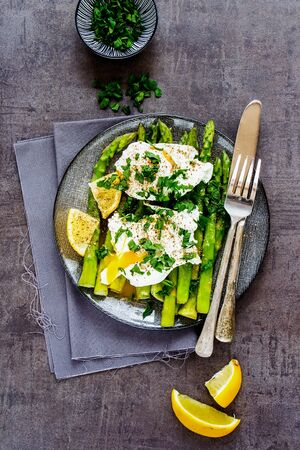 Flat-lay of plate with aspargus and poached eggs on vintage board  Stock Photo