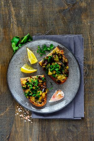 Plate with oven-roasted warm aubergine salad on grilled bread