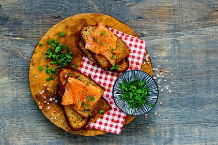 Fresh herbs with smoked salmon on grilled bread on wooden cutting board Stock Photo