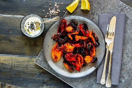 Baked sweet peppers with yogurt dressing in plate top view Stock Photo