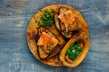 Smoked salmon and fresh herbs on grilled bread on wooden cutting board Stock Photo