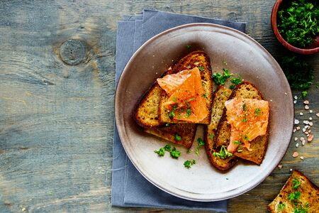 Smoked salmon and fresh herbs on grilled bread in plate flat lay Stock Photo