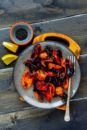 Flat-lay of roasted sweet peppers in plate on dark wooden table