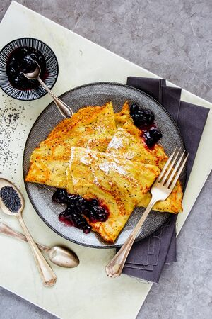 Flat-lay of poppyseed pancakes with wild blueberry jam on light background Stock Photo