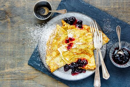 Poppyseed pancakes with wild blueberry jam on wooden table