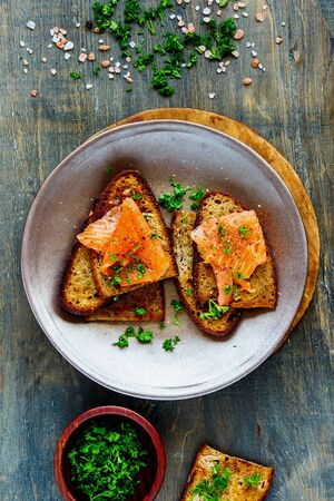 Grilled bread with smoked salmon and fresh herbs in plate flat lay Stock Photo