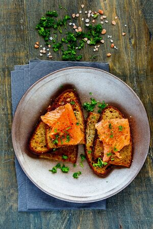 Smoked salmon and fresh herbs on grilled bread on wooden background flat lay