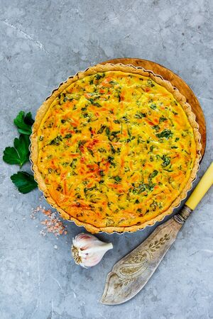 Delicious cheese quiche with herbs on light background flat lay