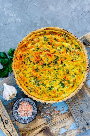 Traditional cheese quiche with herbs on light background Stock Photo