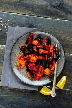 Roasted sweet peppers in plate on dark wooden table flat lay Stock Photo
