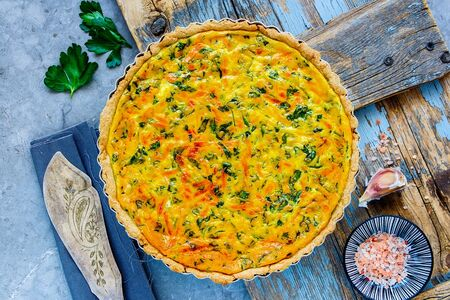 Fresh classic cheese quiche with herbs on light background