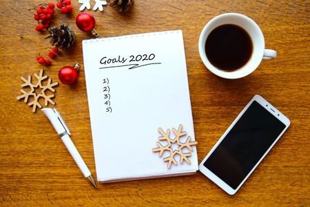 Flat lay photo with Christmas decorations, coffe cup, phone and open note book with the text Goals 2020. New Year eve concept