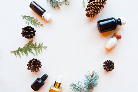 Cosmetic bottles, cones and spruce branches on white background, top view. Natural cosmetic products concept