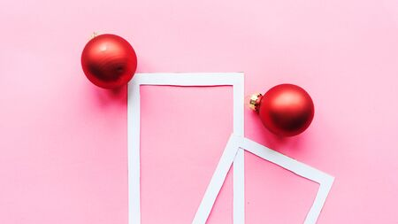 Christmas composition. Photo frame and red baubles on pink background. Christmas, winter, new year concept. Flat lay, top view, copy space