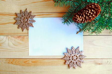 White mockup blank, Christmas tree branches and Christmas decorative snowflakes on wooden background. Flat lay, top view, copy space. Xmas greeting card Stock Photo