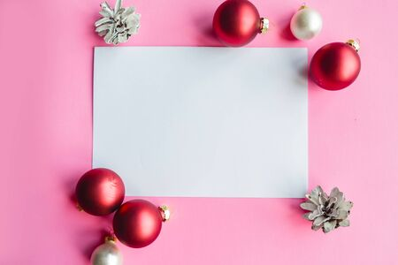 Christmas composition. White mockup blank and Christmas decorations on pink background. Christmas, winter, new year concept. Flat lay, top view, copy space