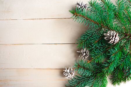 Spruce branches with pinecones on wooden background. Flat lay, top view, copy space Imagens